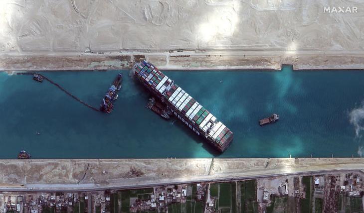 Munkagépekkel és vontatóhajókkal próbálják kiszabadítani a keresztbe fordult és beszorult Ever Given nevű konténerszállítót a Szuezi-csatornában 2021. március 28-án. (Fotó: MTI/EPA/Maxar Technologies)