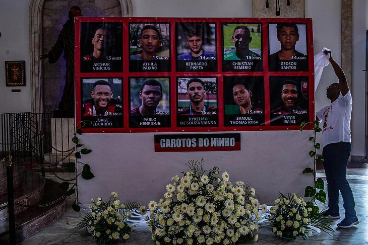 Egy munkás megpróbálja eltakarni a Flamengo fotómontázsát, melyen a tűz áldozatai mellett véletlenül az egyik túlélő portréja is szerepel. (Fotó: New York Times)