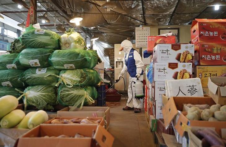 Védőruhát viselő egészségügyi alkalmazottak fertőtlenítenek a tüdőgyulladást okozó új koronavírus-járvány elleni védekezésül egy szöuli piacon (Fotó: MTI/AP/Ri Dzsin Man)