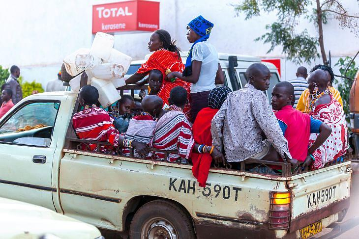Emberek egy furgon platóján Kenyában. (Depositphotos)