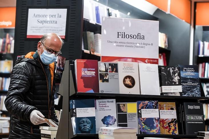 Védőmaszkos vásárló egy római könyvesboltban 2020. április 20-án. Az olasz kormány a hónap közepén elkezdte a koronavírus-járvány ellen bevezetett korlátozó intézkedések enyhítését. MTI/EPA/ANSA/Angelo Carconi