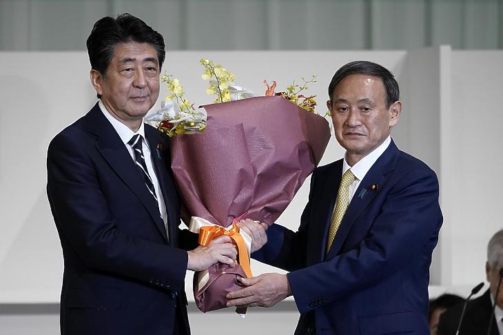 Abe Sindzó japán miniszterelnök (b) virágot nyújt át Szuga Josihide kormányszóvivőnek, miután utóbbi megnyerte a japán kormánypárt, a Liberális Demokrata Párt (LDP) új vezetőjének megválasztására kiírt szavazást Tokióban 2020. szeptember 14-én. (Fotó: MTI/AP pool/Eugene Hoshiko)