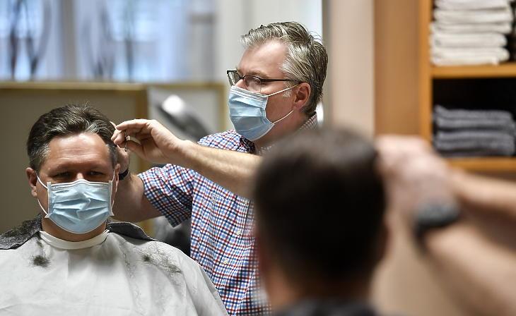 Hajat vágnak egy vendégnek egy gelsenkircheni fodrászüzletben 2021. március 1-jén. Mától már kozmetikushoz is lehet menni Németországban. (Fotó: MTI/AP/Martin Meissner)