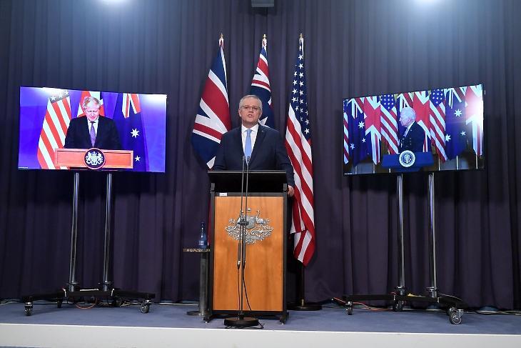 Hibrid sajtótájékoztató - a bal oldali képernyőn Boris Johnson brit miniszterelnök, a jobb oldalin Joe Biden, az USA elnöke, középen pedig Scott Morrison ausztrál miniszterelnök Canberrában 2021. szeptember 16-án az új védelmi szövetség bejelentésekor. Fotó: EPA / Mick Tsikas