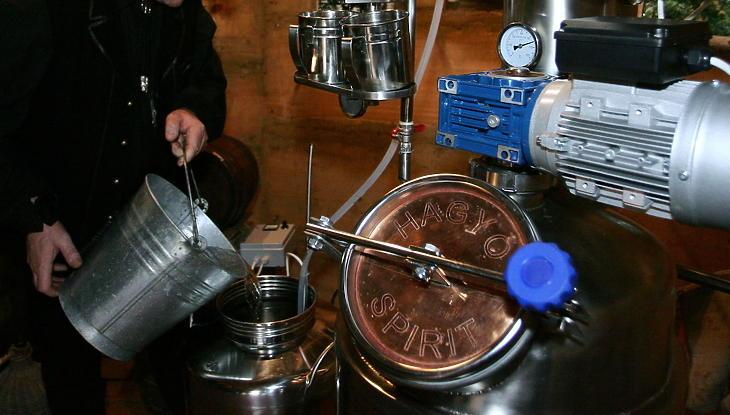 Pálinkafőző szakember hűtővizet önt egy lepárló berendezésbe. Illusztráció. (MTI Fotó: Varga György)