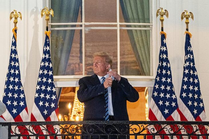 Donald Trump leveszi szájmaszkját, miután visszatért a washingtoni Fehér Házba a Maryland állambeli Bethesdában lévő Walter Reed katonai kórházból 2020. október 5-én. (Fotó: MTI/EPA /Pool/Ken Cenedo)