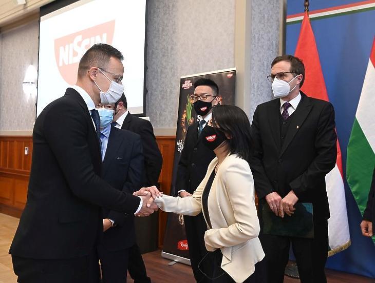 Szijjártó Péter külgazdasági és külügyminiszter és Kurata Aya, a Nissin Foods Kft. igazgatója kezet fog a kft. beruházásbejelentő sajtótájékoztatóján (Fotó: MTI/Bruzák Noémi)