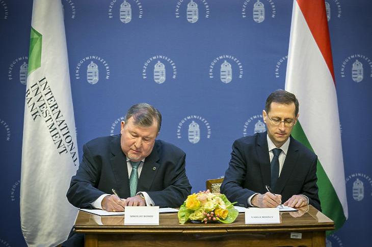 Varga Mihály pénzügyminiszter (j) és Nyikolaj Koszov, a Nemzetközi Beruházási Bank (NBB) elnöke aláírja a nemzetközi pénzintézet székhelyének áthelyezéséről szóló megállapodást Budapesten, a Pénzügyminisztériumban (Forrás: MTI)