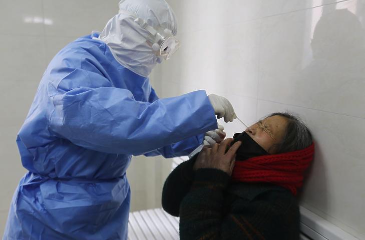 Lázas nőtől vesz orrváladékminát egy ápoló a kínai Santung tartományban fekvő Jinan megye egyik kórházában 2020. február 12-én. MTI/EPA/Featurechina