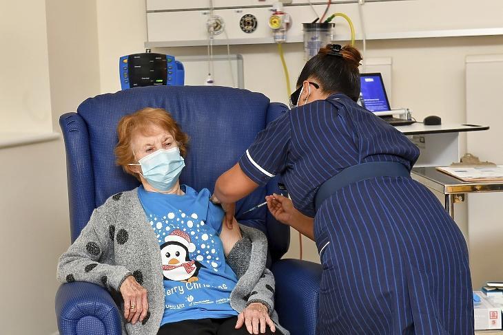 A 90 éves Margaret Keenan megkapja a Pfizer-BioNTech oltóanyagkifejlesztő vállalatok koronavírus elleni vakcináját az angliai Coventry egyik kórházában 2020. december 8-án. Az Egyesült Királyságban ezen a napon megkezdték az új típusú koronavírus elleni tömeges oltási kampányt. Keenan volt az első páciens, akinek beadták az oltást. MTI/PA pool/AP/Jacob King