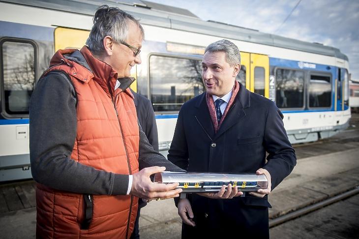 Lázár János, a Hódmezővásárhely-Szeged tram-train mintaprojektért felelős kormánybiztos átveszi Dunai Zoltántól, a Stadler Trains Magyarország Kft. ügyvezető igazgatójától egy tram-train szerelvény makettjét az első vasút-villamost bemutató sajtótájékoztatón 2021 januárjában. A társaság a jövőben a Mészáros csoporttal együtt gyárt majd vasúti kocsikat. Fotó: MTI/Ujvári Sándor