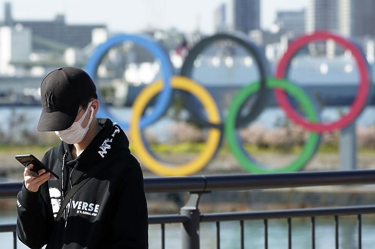 Egészségügyi maszkot viselő fiú az olimpiai játékok szimbóluma, az öt karika előterében, Tokió Odaiba városrészében 2020. március 3-án. MTI/AP/Eugene Hoshiko