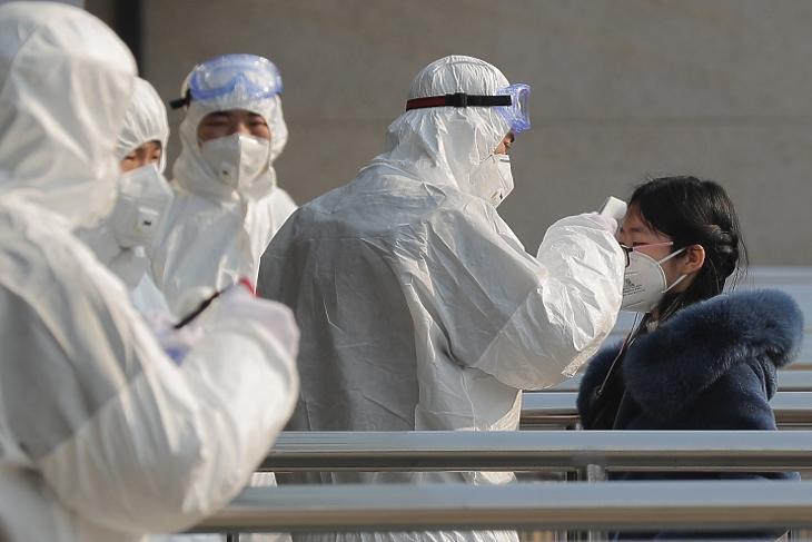 Védőruhába öltözött egészségügyi alkalmazottak egy utas hőmérsékletét vizsgálják egy pekingi metróállomáson 2020. január 25-én. MTI/EPA/Vu Hong