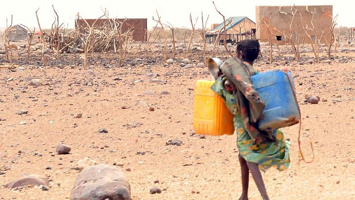 Egy lány Mauritánia délkeleti részén kannákat cipel, hogy megtöltse azokat vízzel. (Fotó: Abdelhak Senna)