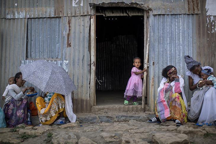 Kislány áll az Etiópia északi Tigré tartományában kialakult konfliktus miatt lakóhelyük elhagyására kényszerült emberek számára létesített belföldi menekülttábor fogadóközpontjának bejáratában Tigré tartomány székhelyén, Mekelében 2021. május 9-én. (Fotó: MTI/AP/Ben Curtis)