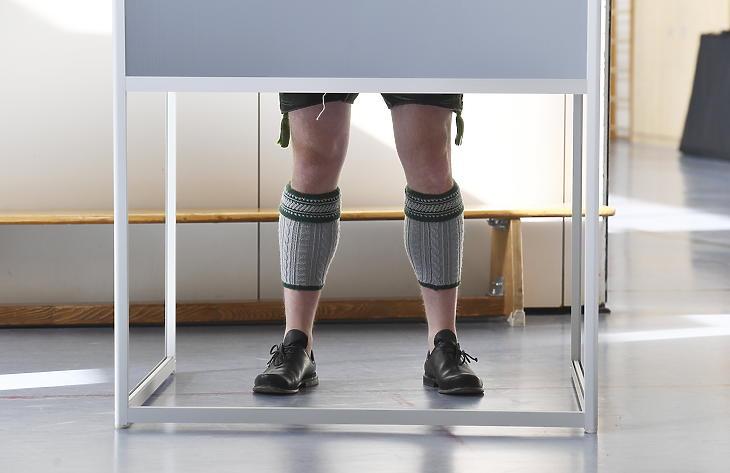 Hagyomásnyos bajor öltözetet viselő férfi áll egy szavazófülkében a német szövetségi parlamenti választáson Garmisch-Partenkirchenben 2021. szeptember 26-án. (Fotó: MTI/AP/dpa/Angelika Warmuth)