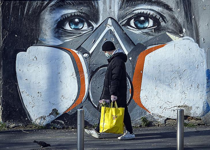 Védőmaszkos embert ábrázoló falfestmény előtt egy járókelő Milánóban 2020. március 16-án, amikor a tüdőgyulladást okozó koronavírus terjedésének megfékezésére vesztegzár van érvényben egész Olaszországban. MTI/EPA/ANSA/Andrea Fasani