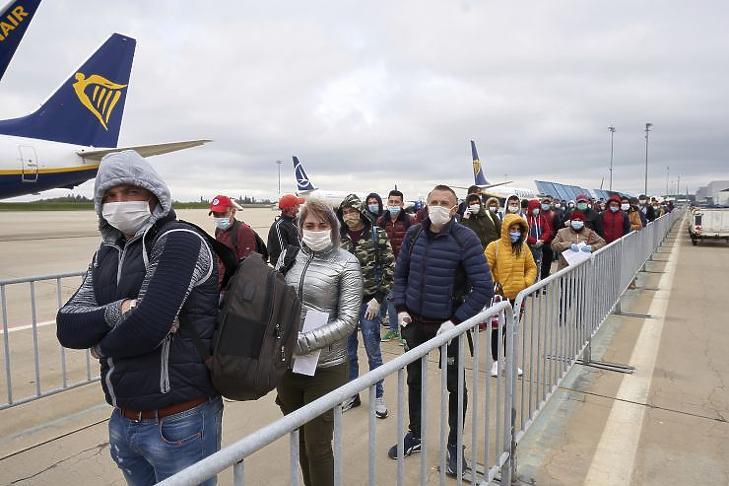 Védőmaszkot viselő román mezőgazdasági idénymunkások érkeznek a németországi Hahn repülőterére (Fotó: MTI/AP/DPA/Thomas Frey)