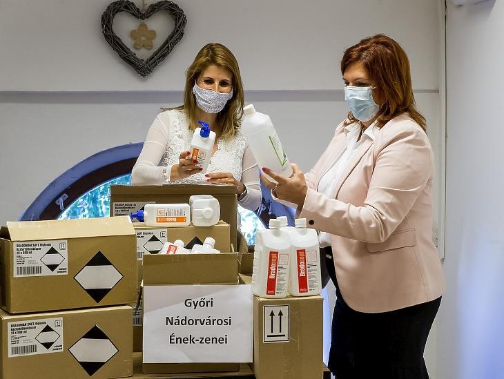Egy iskolaigazgató és kolléganője kézfertőtlenítő szereket és eszközöket vesz át a Győri Nádorvárosi Ének-zenei Általános Iskolában 2020. szeptember 2-án.  MTI/Krizsán Csaba