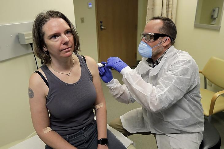 Jennifer Haller amerikai nő az új koronavírus ellen készített, első fokozatban, klinikai kísérleti stádiumban lévő oltóanyagot kap egy gyógyszerésztől a seatlle-i Kaiser Permanente Washington Egészségügyi Kutatóintézetben 2020. március 16-án. MTI/AP/Ted S. Warren