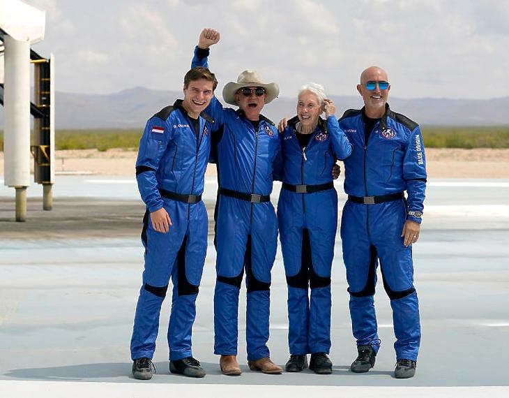 Jeff Bezos és csapata a Blue Origin New Shepard űrrakétája előtt, a texasi Van Horn közelében lévő űrkikötő térségében a sikeres földet érésük után (Fotó: MTI/AP/Tony Gutierrez)