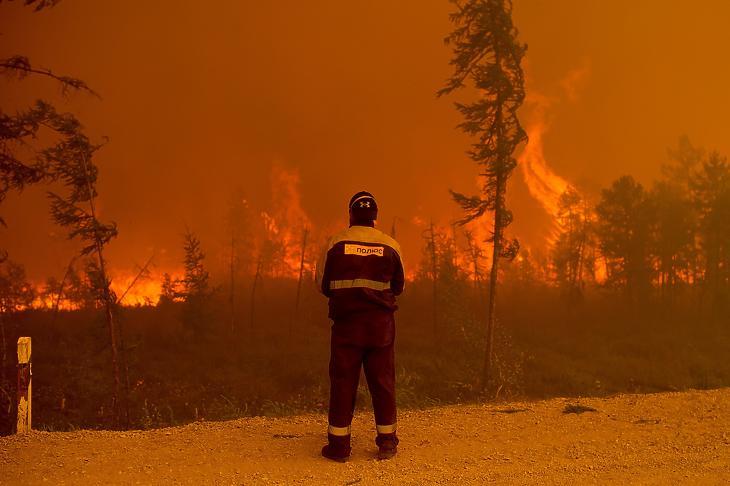 Erdőtüzet figyel egy tűzoltó a jakutföldi Gornij járásban fekvő Kjujoreljah település közelében 2021. augusztus 7-én. (Fotó: MTI/AP/Ivan Nyikiforov)